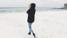 Ung härlig kvinna som går runt om stranden på en kall vinterdag långsam rörelse arkivfilmer
