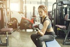 Ung härlig kvinna som gör övningar med hanteln i idrottshall fotografering för bildbyråer