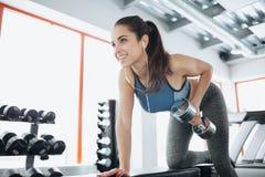 Ung härlig kvinna som gör övningar med hanteln i idrottshall Royaltyfri Foto