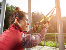 Ung härlig kvinna som gör konditionutbildning med upphängningremmar Royaltyfria Foton
