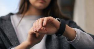 Ung härlig kvinna som gör olika gester med ett finger på en pekskärm av en wearable apparat för smartwatch som är smart lager videofilmer