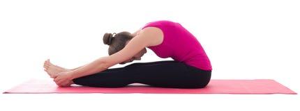 Ung härlig kvinna som gör sträcka övning på matt isolator för yoga Arkivbilder
