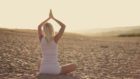 Ung härlig kvinna som gör yoga på kusten av stock video