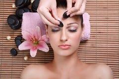 Ung härlig kvinna som har ansikts- massage Arkivbild