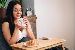 Ung härlig kvinna som har frukosten på säng Royaltyfri Bild