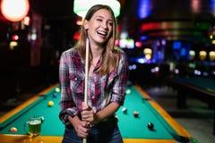 Ung härlig kvinna som har gyckel och spelar billiard i en klubba arkivfoton