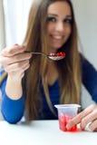 Ung härlig kvinna som hemma äter yoghurt Royaltyfri Fotografi