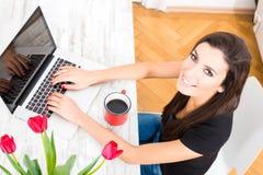 Ung härlig kvinna som hemma använder en bärbar dator royaltyfri fotografi