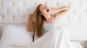 Ung härlig kvinna som hemma gäspar i säng: Koppla av komfortsömnbegreppet royaltyfri fotografi