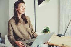Ung härlig kvinna som hemma shoppar direktanslutet med bärbara datorn och koppen kaffe i morgonen Arkivbilder