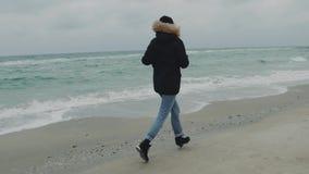 Ung härlig kvinna som kör runt om stranden på en kall vinterdag långsam rörelse stock video