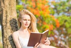 Ung härlig kvinna som läser en bok i natur arkivbilder