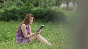 Ung härlig kvinna som läser en bok i natur arkivfilmer