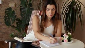 Ung härlig kvinna som läser en bok och tar anmärkningar Kvinna som läser ett boksammanträde i en stol stock video