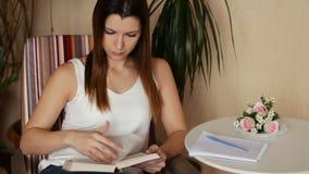 Ung härlig kvinna som läser en bok och tar anmärkningar Kvinna som läser ett boksammanträde i en stol arkivfilmer
