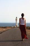 Ung härlig kvinna som långsamt går till den Lock de Barberias fyren under en fantastisk sommarsolnedgång Arkivbilder