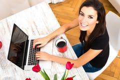 Ung härlig kvinna som ler, medan genom att använda en bärbar dator hemma arkivbild