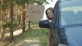 Ung härlig kvinna som liftar att stå på vägen med en ryggsäck på en tabell med en inskrift som ÄR SÖDRA i en bil lager videofilmer
