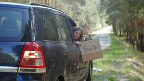 Ung härlig kvinna som liftar att stå på vägen med en ryggsäck på en tabell med en inskrift som ÄR SÖDRA i en bil stock video