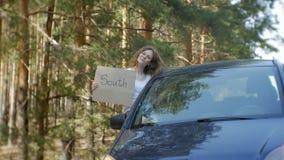 Ung härlig kvinna som liftar att stå på vägen med en ryggsäck på en tabell med en inskrift som ÄR SÖDRA i en bil arkivfilmer