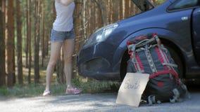 Ung härlig kvinna som liftar att stå på vägen med en ryggsäck på en tabell med en inskrift som ÄR SÖDRA nära a arkivfilmer