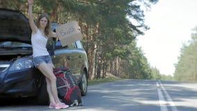 Ung härlig kvinna som liftar att stå på vägen med en ryggsäck på en tabell med en inskrift som ÄR SÖDRA nära a lager videofilmer