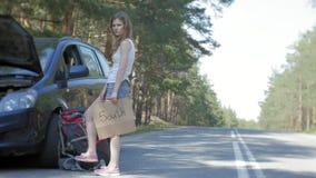 Ung härlig kvinna som liftar att stå på vägen med en ryggsäck på en tabell med en inskrift som ÄR SÖDRA nära a stock video