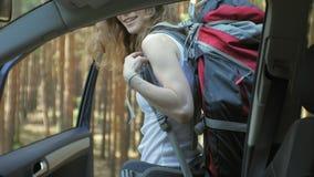 Ung härlig kvinna som liftar att stå på vägen med en ryggsäck på en tabell med en SÖDRA inskrift arkivfilmer