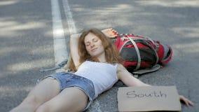 Ung härlig kvinna som liftar att stå på vägen med en ryggsäck på en tabell med en SÖDRA inskrift stock video