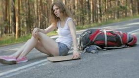 Ung härlig kvinna som liftar att stå på vägen med en ryggsäck på en tabell med en SÖDRA inskrift lager videofilmer