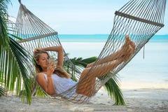 Ung härlig kvinna som ligger i en hängmatta med telefonen Royaltyfri Foto