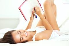 Ung härlig kvinna som ligger i säng som skriver en dagbok Royaltyfria Bilder