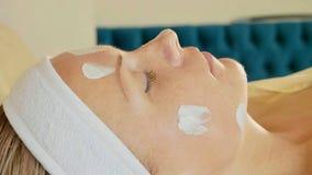Ung härlig kvinna som ligger med ansiktsbehandlingkräm på framsidan på brunnsortsalongen Royaltyfri Fotografi