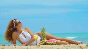 Ung härlig kvinna som ligger vid havet på sanden med orange ny fruktsaft Begreppssemester lager videofilmer