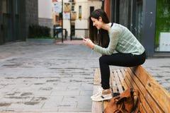Ung härlig kvinna som lyssnar till musik med telefonen i utomhus arkivbilder