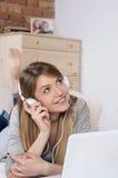 Ung härlig kvinna som lyssnar till musik, medan koppla av hemma Royaltyfri Foto