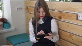 Ung härlig kvinna som pratar med hennes vän på hennes mobiltelefon med ett leende stock video