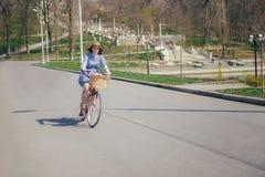 Ung härlig kvinna som rider en cykel i en parkera Aktivt folk Arkivfoto