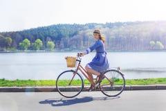 Ung härlig kvinna som rider en cykel i en parkera Aktivt folk Royaltyfria Bilder