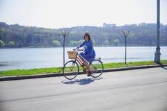 Ung härlig kvinna som rider en cykel i en parkera Aktivt folk Arkivbilder