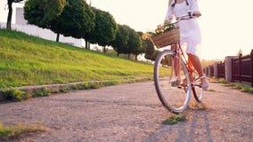 Ung härlig kvinna som rider en cykel på solnedgången långsam rörelse lager videofilmer