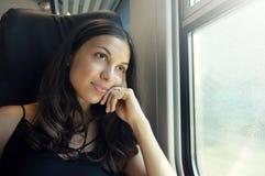 Ung härlig kvinna som ser till och med drevfönstret Resande sammanträde för lycklig drevpassagerare i en plats och se till och me arkivfoto