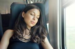 Ung härlig kvinna som sover sammanträde i drevet Utbilda resande sammanträde för passageraren i en plats och sova royaltyfri foto