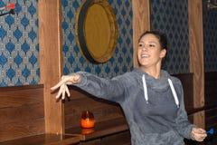 Ung härlig kvinna som spelar pilar i en klubba royaltyfri bild