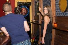 Ung härlig kvinna som spelar pilar i en klubba royaltyfria foton
