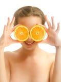 Ung härlig kvinna som täcker henne ögon med orange skivor Fotografering för Bildbyråer