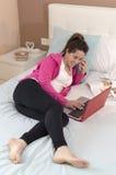 Ung härlig kvinna som talar och arbetar genom att använda bärbara datorn på säng hemma Arkivbild