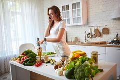 Ung härlig kvinna som talar på smartphonen, medan laga mat i det moderna köket Sunt mat- och bantabegrepp f?rlorande vikt royaltyfri bild