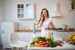Ung härlig kvinna som talar på smartphonen, medan laga mat i det moderna köket Sunt mat- och bantabegrepp f?rlorande vikt arkivfoto