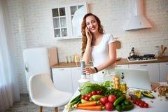 Ung härlig kvinna som talar på smartphonen, medan laga mat i det moderna köket Sunt mat- och bantabegrepp f?rlorande vikt arkivfoton